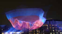 A hanging net being colourful lit in front of the Muziektheater