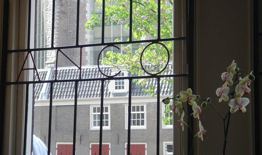 A view through the window with bars vorming the word Anco