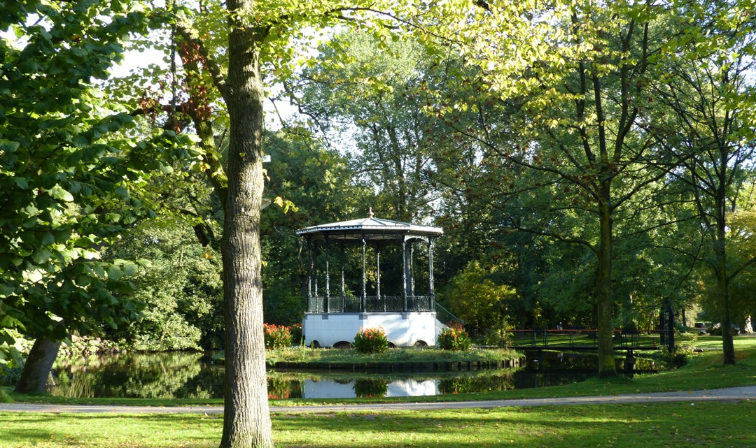 A small white bandstand surrounded by water and a tree in the foreground