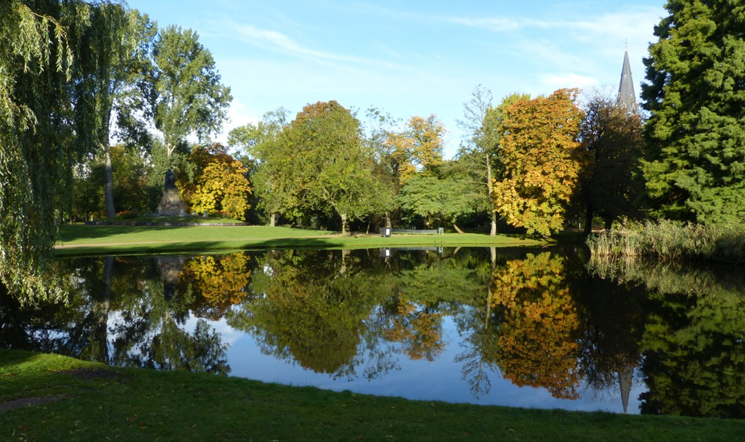 View over a pond reflecting the autumnal coloured trees on the other side