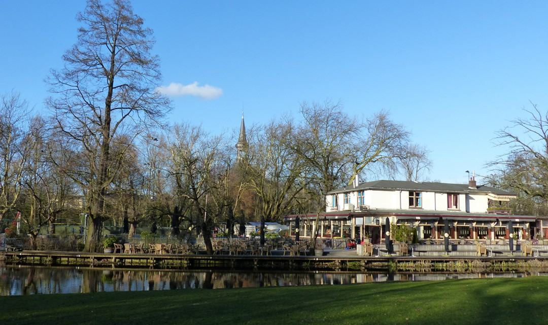 A white restaurant with a veranda all around. Grass and water on the foreground and a small church tower behind the trees in the background