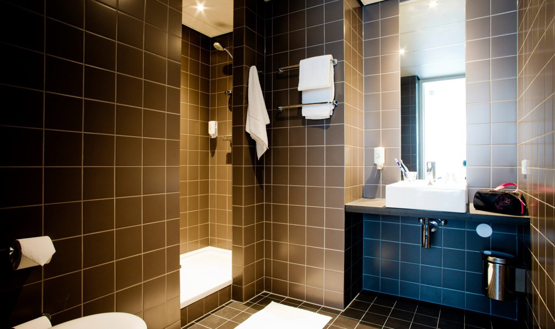 A sober but stylish brown tiled bathroom in the hotel