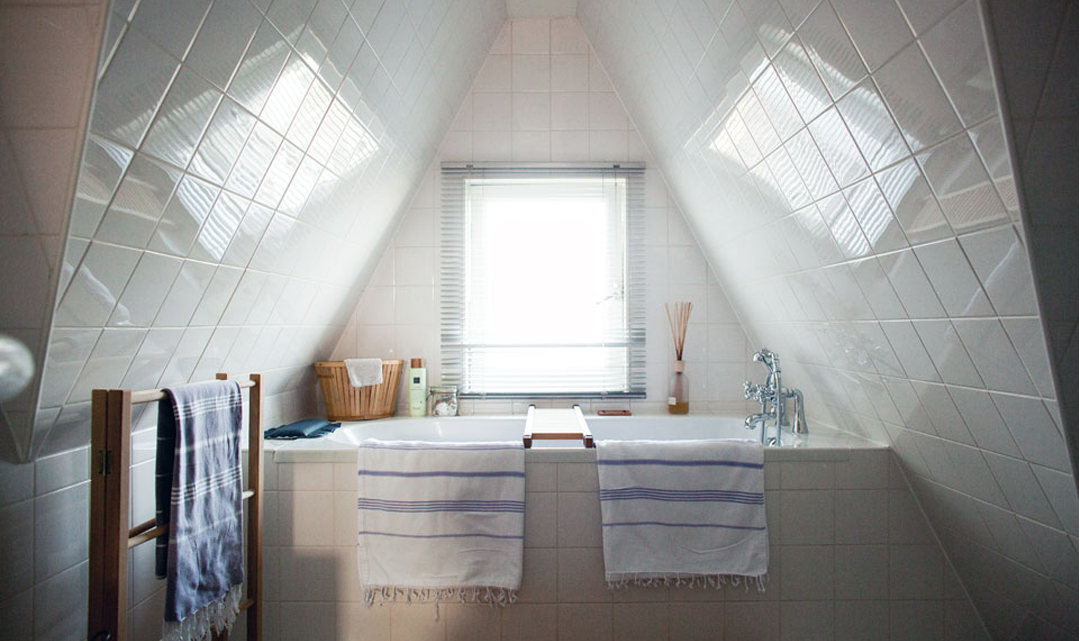 A window above the bath. Towels over the edge of the bath