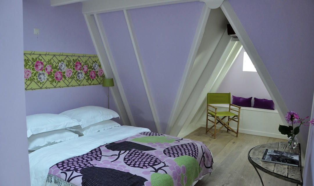 One of the bedrooms, with light purple walls and a bed