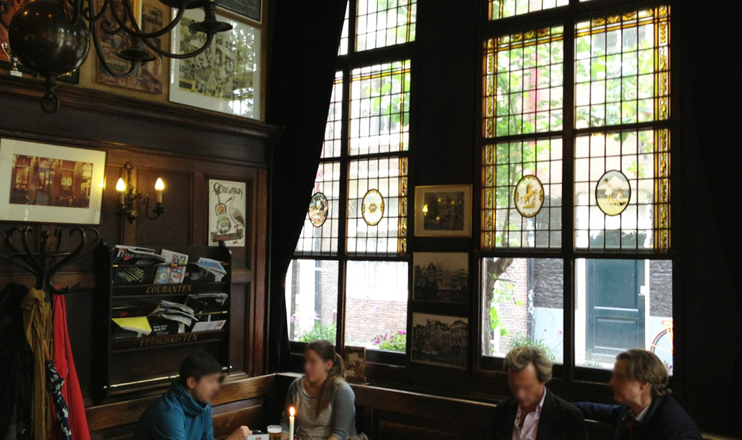 People sitting an chatting at small tables in the dark interior. The windows have stained glass.