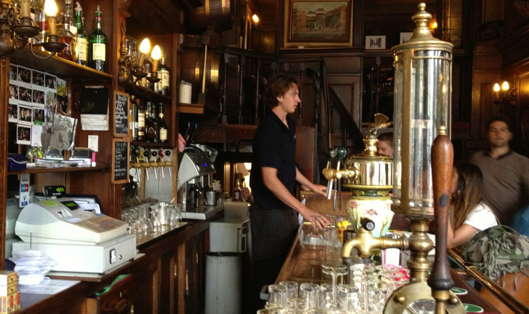 A view behind the bar to the barman. On the bar an original gin tap