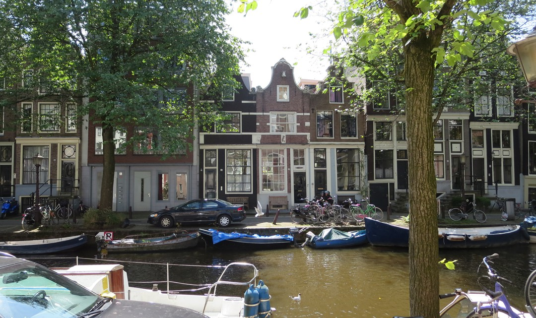 A row of canal houses and boats in the canals in front of them