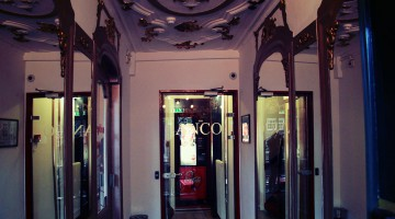 A view from the front door in the hallway with ornamented ceiling and a glass door with the name Anco on it