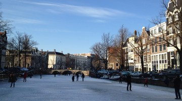 People ice skating on the canals on a blue sky day in winter