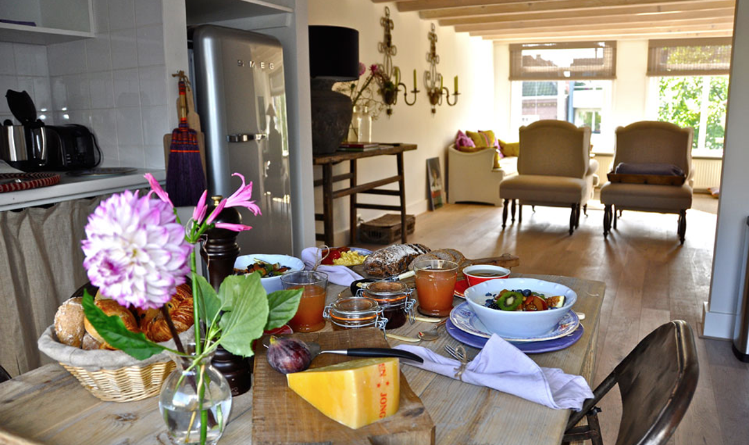 A breakfast table in the foreground and the living room in the background