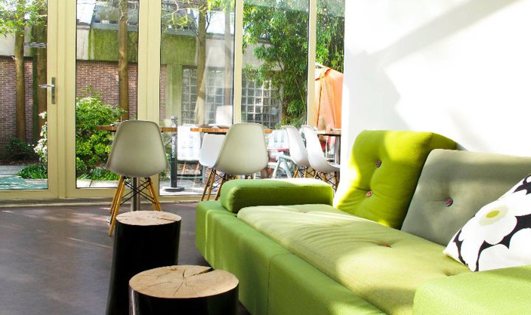 The lounge area with bright green sofa's and a view on the garden