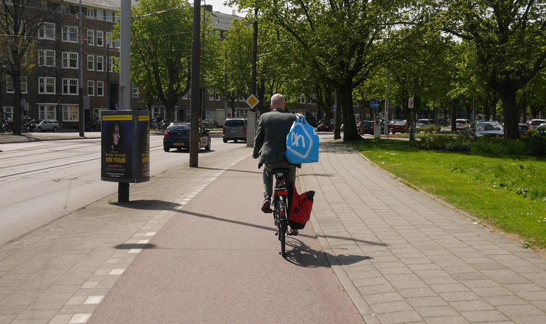Man on bike with shopping bag in his hand