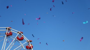 Quarter of a ferris wheel with confetti streamers flying through the air