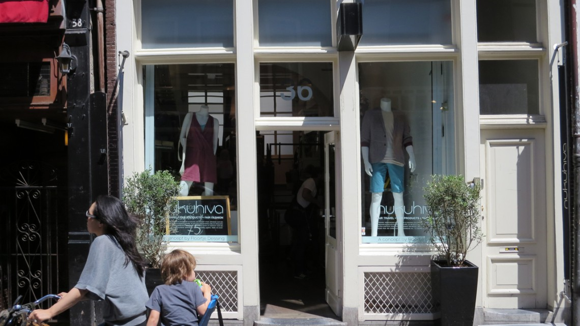 Shop front on a sunny day, with large plants next the door and a woman and child on a bike zooming by