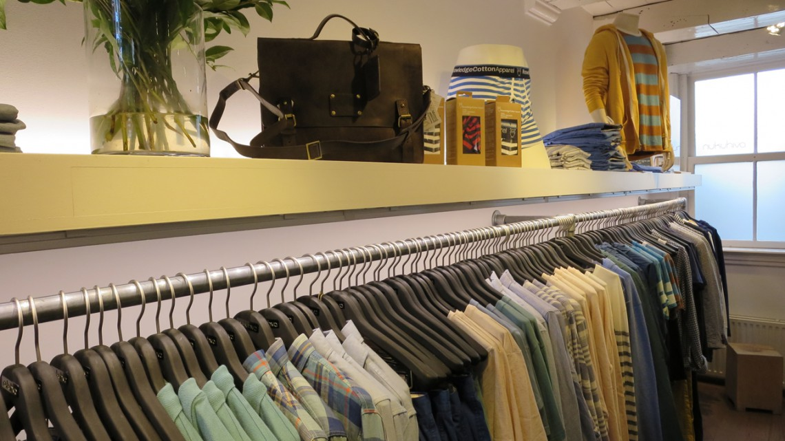 Flowers, a bag and accessories on a shelf above a rack of dress shirts
