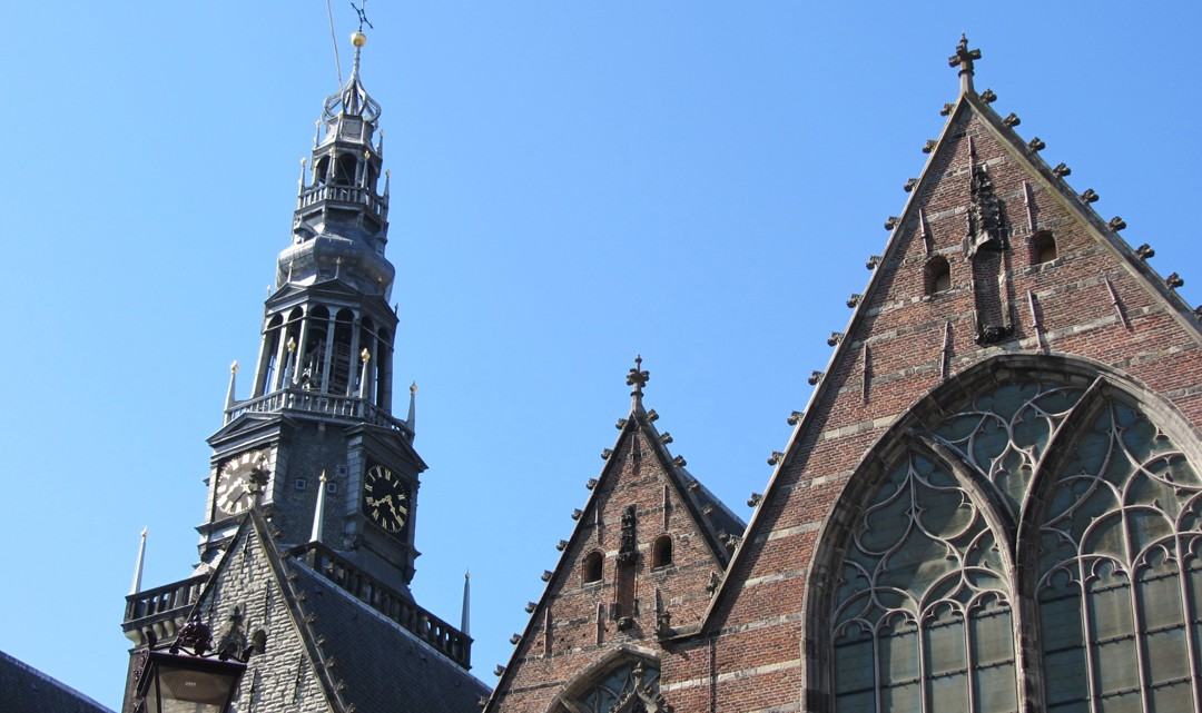Top gables and spire of the old church against a blue sky
