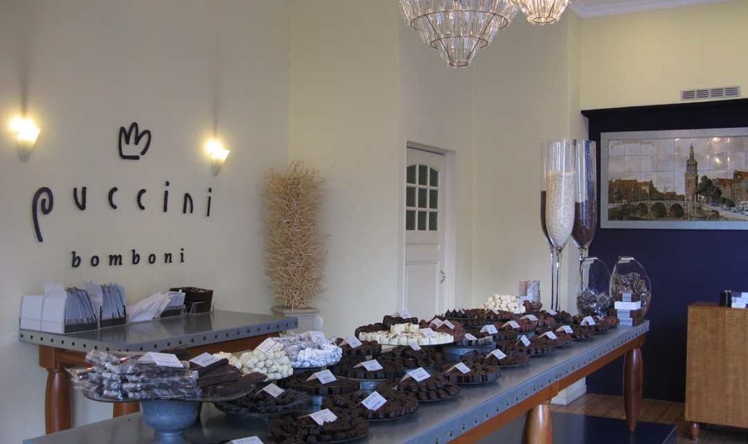 A table full of chocolate on trays. Against the wall the logo of Puccini Bomboni