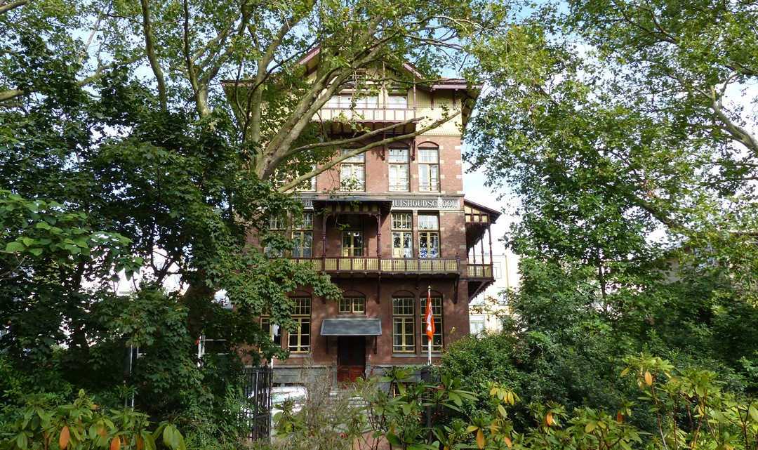The historic chalet-style building through the trees and bushes of Vondelpark