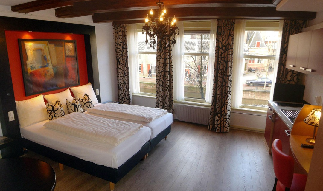 A classy looking bedroom with wooden floor, a chandelier, expose ceiling beams and a view on the canal