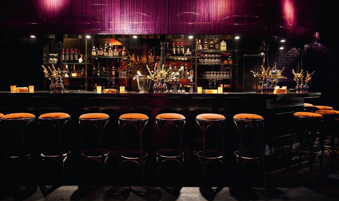A glamorously gloomy bar in black and purple. Small vases with flowers all over the bar