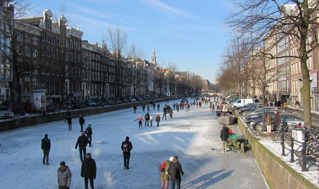 People ice skating on the Keizersgracht on a sunny day
