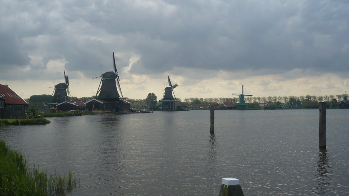 Four windmills along the river on a greyish day