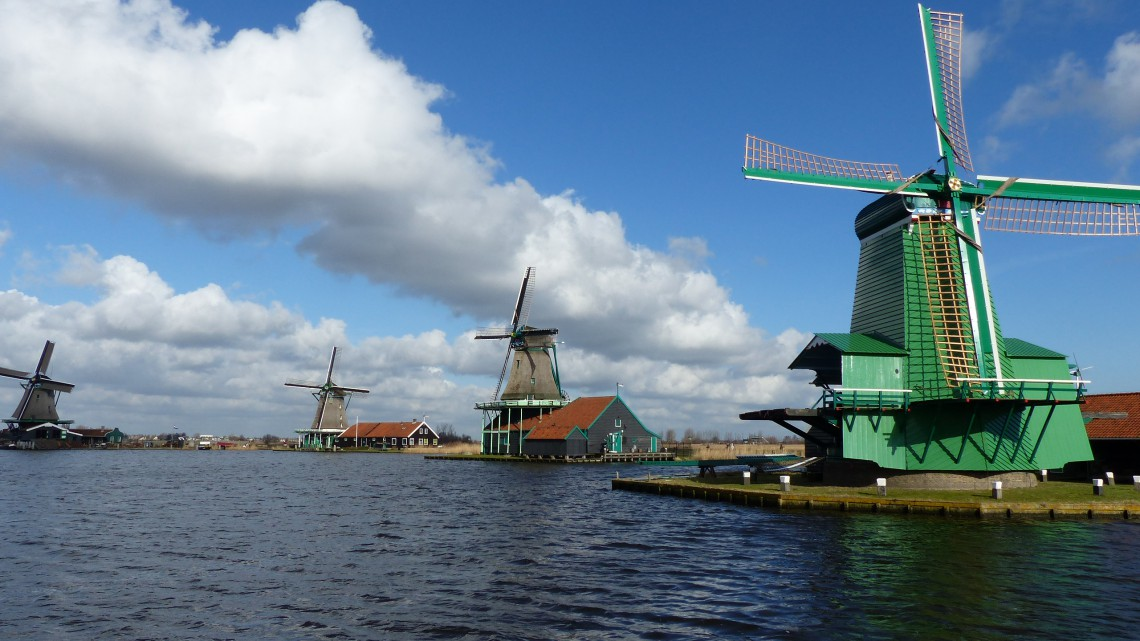 Four windmills in a row along the river in vivid colours against the blue sky