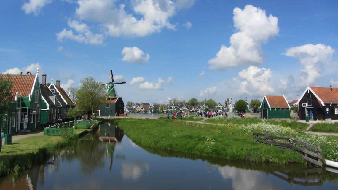 A view over the water with a blue Dutch sky with friendly clouds, a windmill in the background and typical Zaanse houses left and right