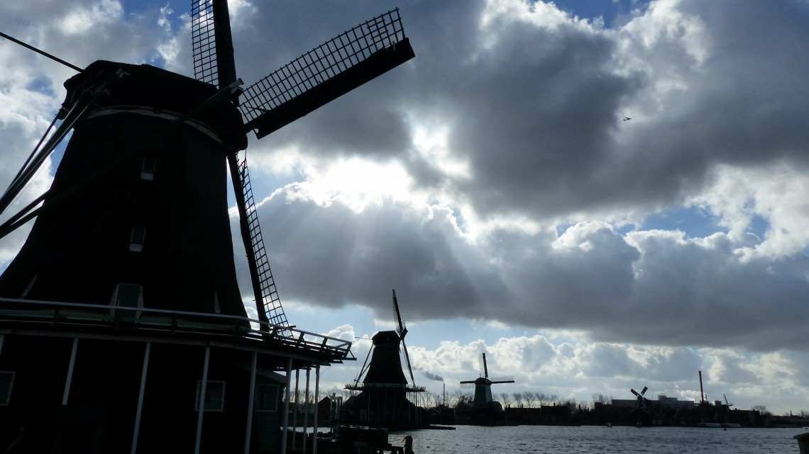Three dark silhouettes of windmills against a cloudy sky and sunshine peeping through