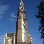 Westertoren with rainbow flag alongside against a blue sky