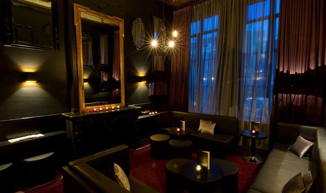 A sophistic, gloomy atmosphere, black leather couches, a fireplace with a very large Baroque framed mirror and a small black chandelier