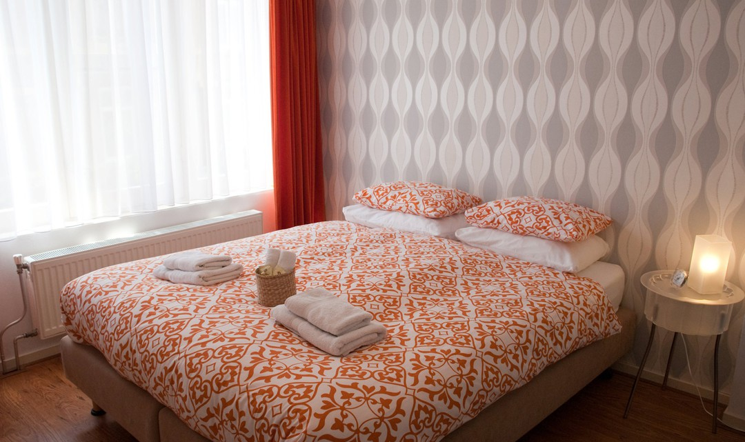 A bed with an orange patterned duvet