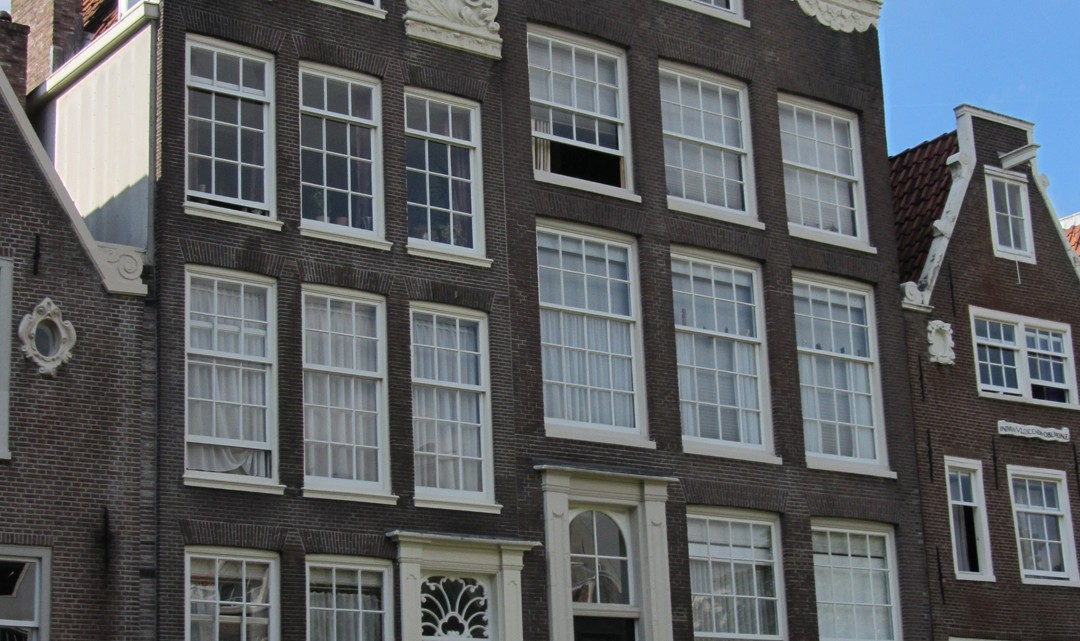 Two typical Amsterdam gable houses with many windows that are divided in smaller square glass