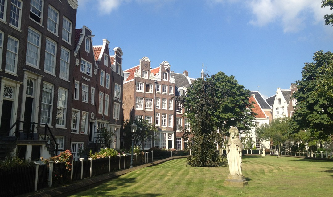 Green grass surrounded with typical Amsterdam gable houses. Trees and a statue sit in the middle of the garden
