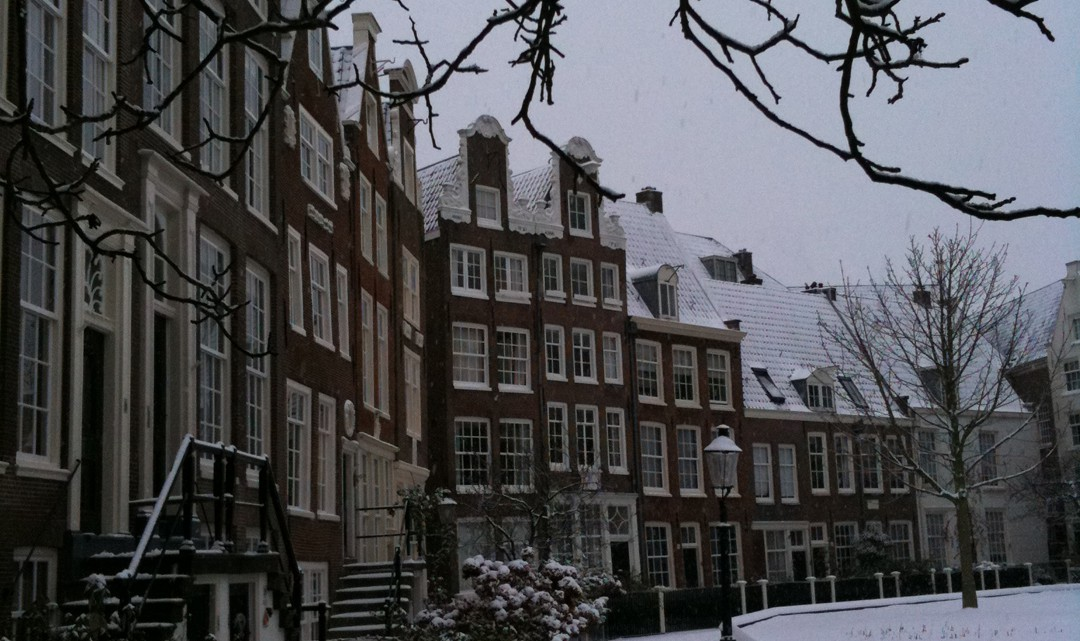 A row of typical Amsterdam gable houses of the Beguinage, in the snow
