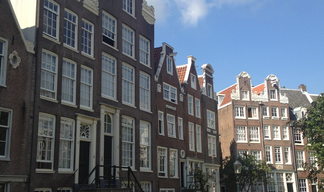 A row of typical Amsterdam gable houses surrounding the grass field of the Beguinage