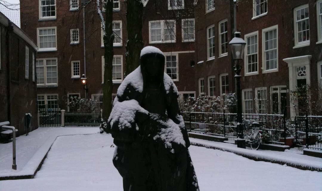 A statue of a Beguinage woman. The statue looks cold and alone in the snow