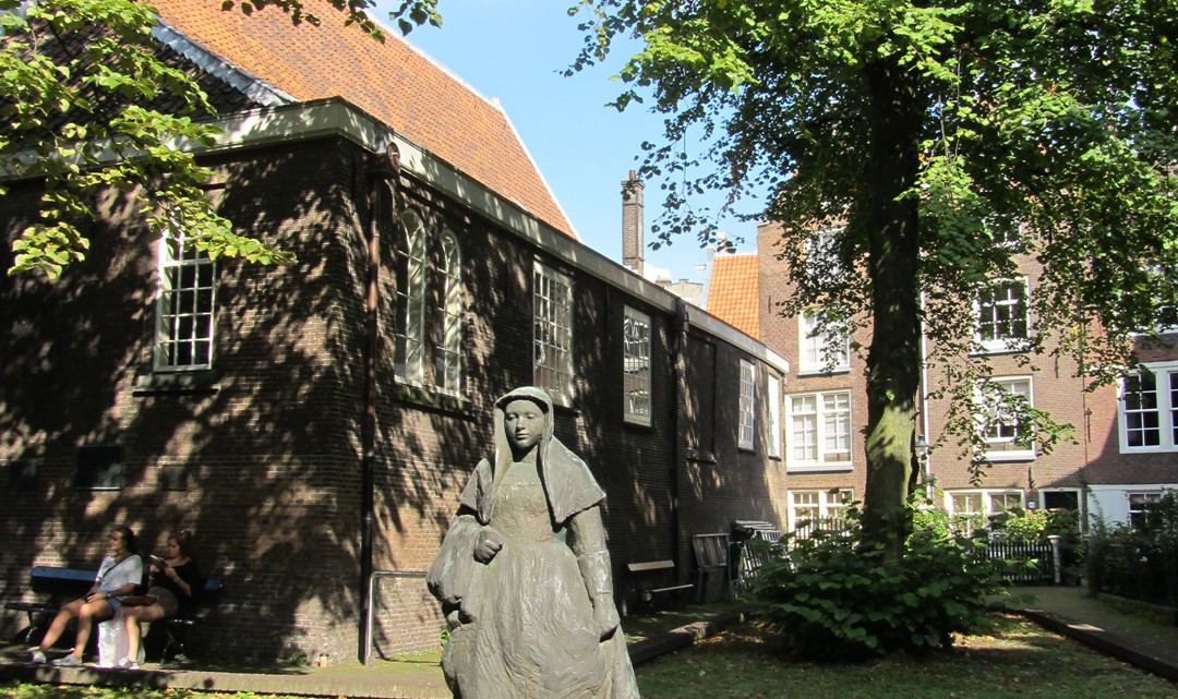 A statue of a Beguinage woman. The statue basks in the sun