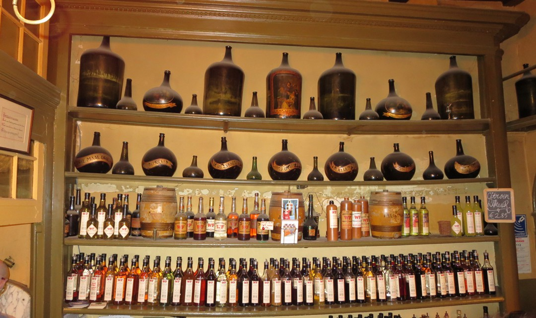 Heavy bottles of liqueur and gins behind the counter on sagging shelves