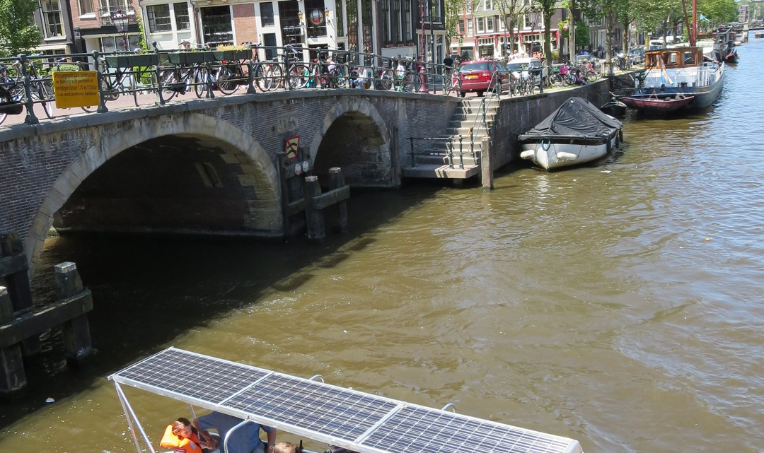 A solar-panelled electric boat seen from above. With typical Amsterdam canal houses in the background