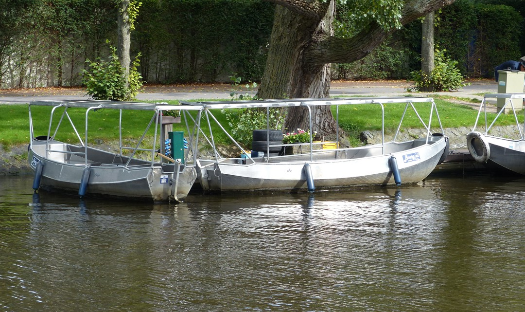 Two electric boats docked along the canal, near a tree