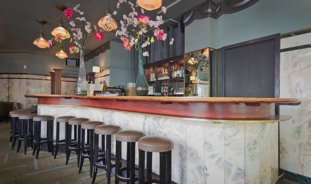 A row of barstools along a curvy bar and high vases with flowers on the light wooden bench top