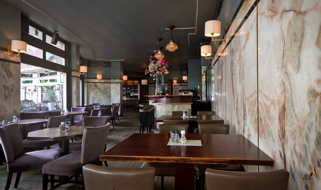 An overview of the restaurant area: dark wooden tables and brown chairs, against a white-pink marble wall