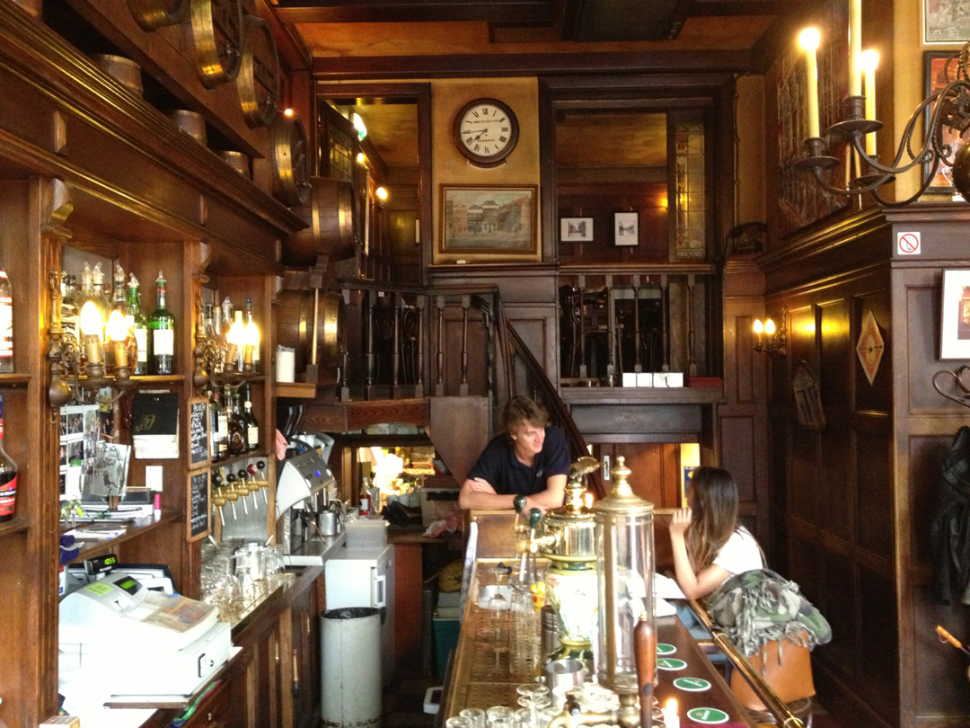 A View Behind The Bar With Lots Of Wood Paneling And Original Features