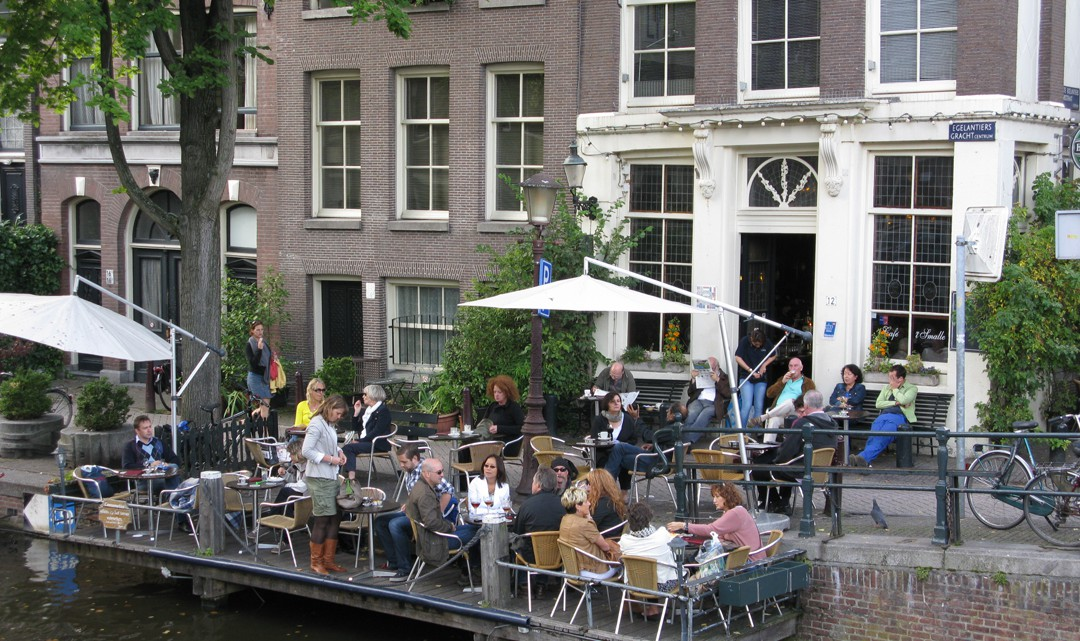 People sitting on the terrace that hangs over the water of the canal