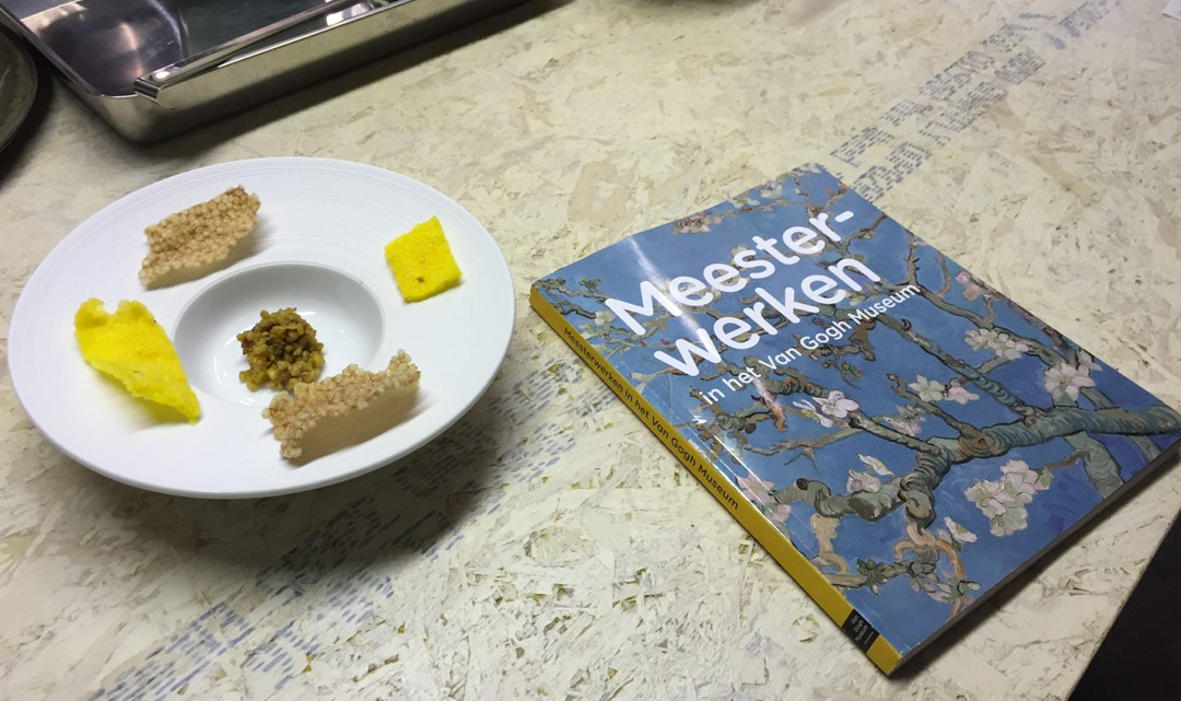 A plate next to a book about Van Gogh's paintings