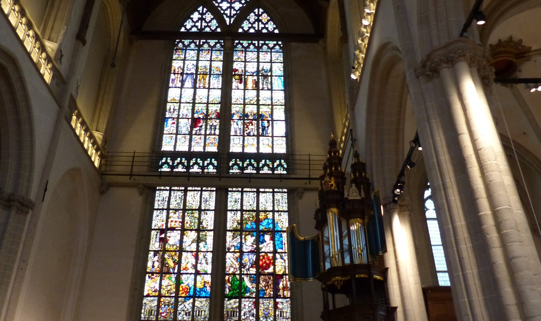 An enormous stained glass window with the small dark wooden organ to the right