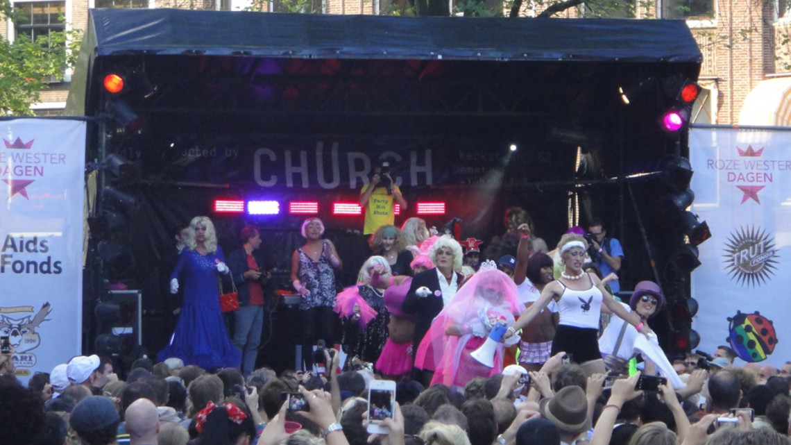 Drag queens and kings walk on stage
