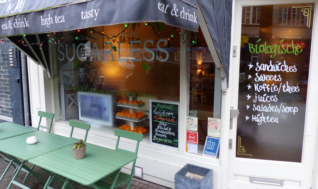 The entrance door to Sugarless with left, in front of the window a few green tables