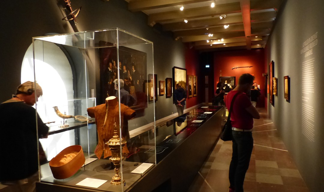 One of the exhibition rooms with paintings on the wall and various artefacts iin a display in the middle of the room